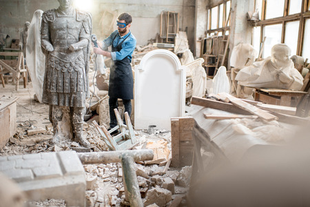 Sculptor working with big stone figure grinding with electirc grinder in the old atmospheric studio with different sculptures on the background