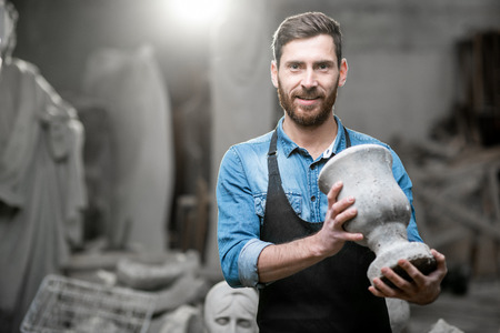 Portrait of a handsome sculptor in blue t-shirt and apron holding old vase in the studio with sculptures on the background Stock Photo