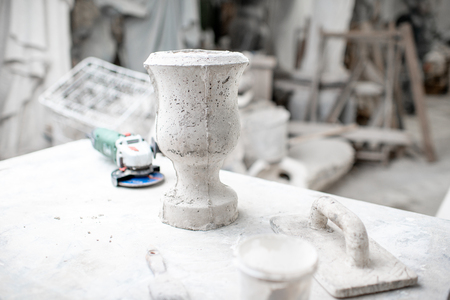 Working place with old sculptures and working tools on the table in the sculptors studio