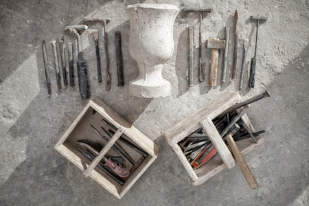 Sculptors working tools with old vase on the floor