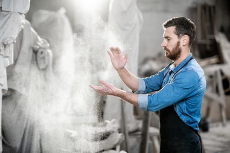 Sculptor clapping hands shaking the dust after the work in the studio with sculptures on the background