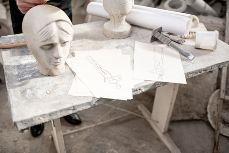 Working place with old sculptures, working tools and drawings on the table in the sculptors studio