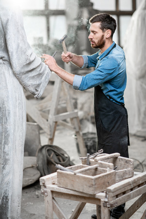 Handsome smoking sculptor beating stone sculpture with hammer and chisel in the studio