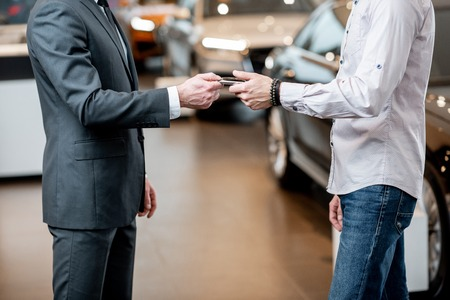 Salesperson giving keychain to a male client at the showroom with modern cars on the background, Close-up with no face