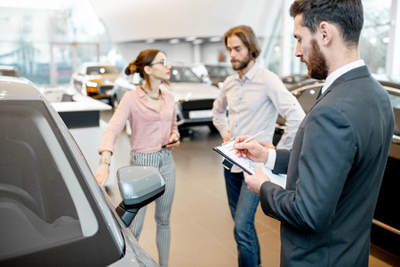 Manager filling test drive documents standing with young couple clients in the showroom