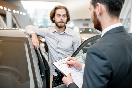 Manager filling car rental documents standing with male client in the showroom