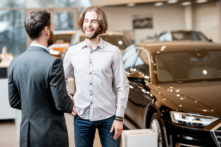 Car salesman helping a young male client to make a decision talking together at the showroom with luxury cars