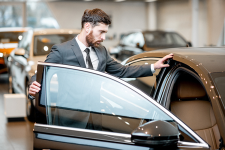 Elegant businessman choosing new luxury car looking at the car intreior in the showroom Stockfoto