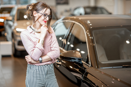 Young beautiful woman hesitates choosing a new car in the showroom Stock Photo