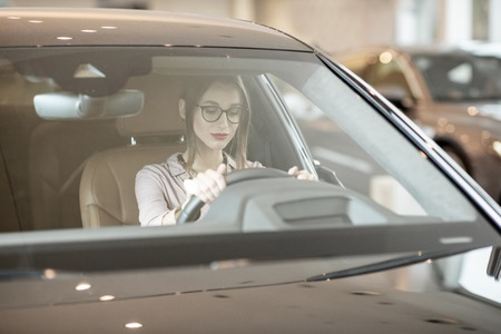Young woman choosing a new car sitting on the driver seat of a luxury car in the showroom