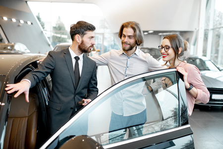 Car salesman showing car interior to a young couple clients in the showroom