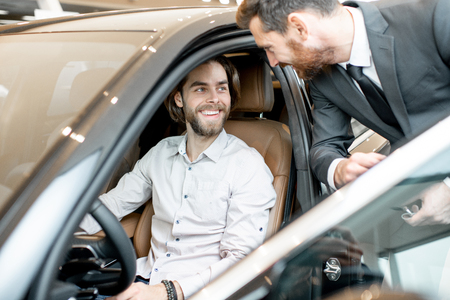 Young man trying a new car sitting on the driver seat talking with salesperson in the showroom
