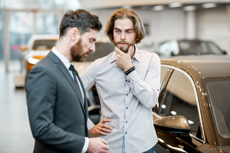 Man client hesitates choosing a car with salesperson in the showroom