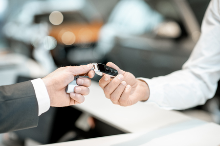 Salesperson giving a keychain from a new car to a client at the stand in the car showroom, close-up view with no face Stockfoto