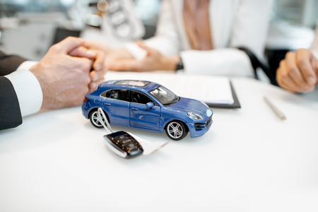 Close-up of a toy car with keychain and clients hands on the table of the car showroom Stockfoto