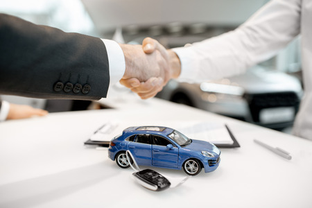 Close-up of a handshake at the table with toy car and keys. Car buying concept Stockfoto