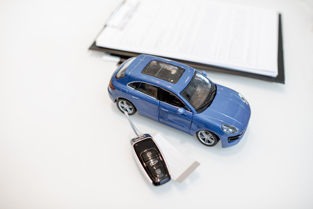 Close-up of a toy car with keychain and documents on the white table Stockfoto