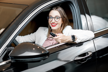 Portrait of a happy owner sitting with keychain on a driver seat of a new luxury car at the showroom