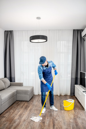 Man as a professional cleaner in blue uniform washing floor with mopping stick and bucket in the living room of the apartment