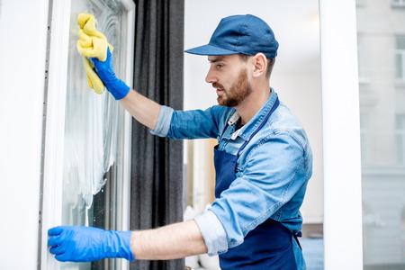 El hombre como un limpiador profesional en uniforme azul de la ventana de lavado con un limpiador de algodón en interiores Foto de archivo