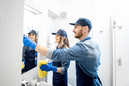 Couple as a professional cleaners in blue uniform cleaning bathroom. Cleaning service concept