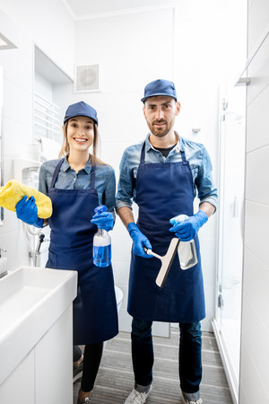 Portrait of a young couple as a professional cleaners in blue uniform cleaning bathroom. Cleaning service concept Imagens