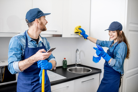 Man and woman as a professional cleaners in uniiform having fun during the work on the kitchen Stockfoto