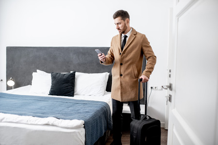Dressed businessman standing with a suitcase and calling phone in the hotel room before the check out