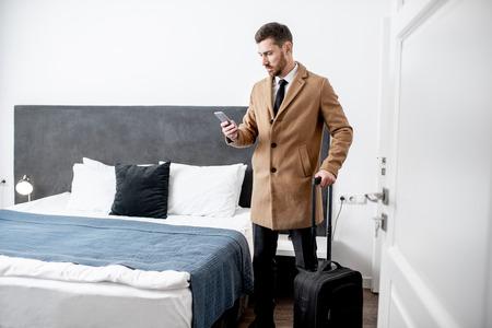 Gekleideter Geschäftsmann, der mit einem Koffer steht und vor dem Check-out im Hotelzimmer telefoniert? Standard-Bild