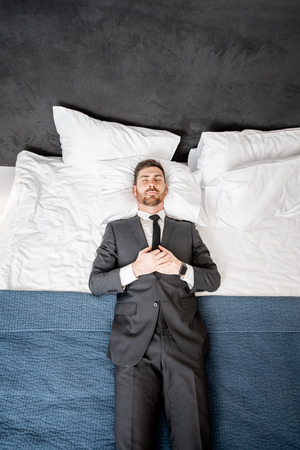 Businessman in the suit lying on the bed like a dead man at the hotel room or bedroom