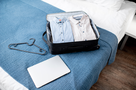 Suitcase full of clothes with laptop on the bed of the hotel room or bedroom. Business trip concept Stock Photo