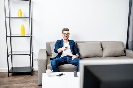 Handsome businessman dressed casually watching TV on the couch at home Stock Photo
