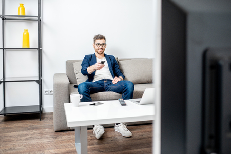 Handsome businessman dressed casually watching TV on the couch at home Stockfoto