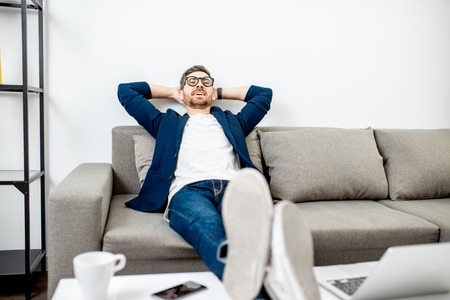 Businessman dressed casually relaxing on the couch while watching TV at home Stockfoto