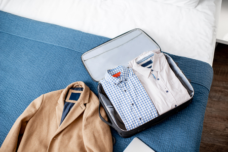 Suitcase full of clothes with coat on the bed of the hotel room or bedroom. Business trip concept Stock Photo