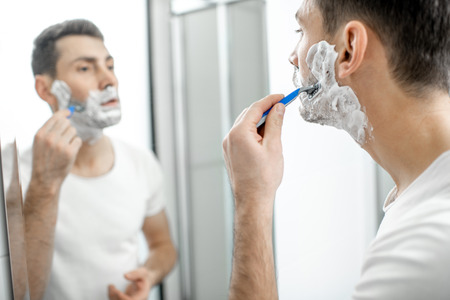 Handsome man in white t-shirt shawing his beard with blade and foam in the bathroom 写真素材