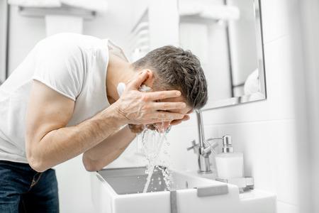 Hombre lavándose la cara con agua dulce y espuma en el lavabo del baño blanco Foto de archivo