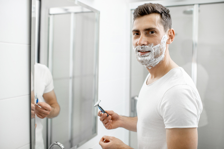 Portrait of a handsome man in white t-shirt shawing with blade and foam in the bathroom