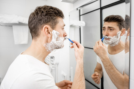 Handsome man in white t-shirt shawing his mustache with blade and foam in the bathroom