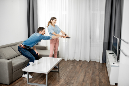 Young couple having a conflict switching a TV channel at home Stock Photo