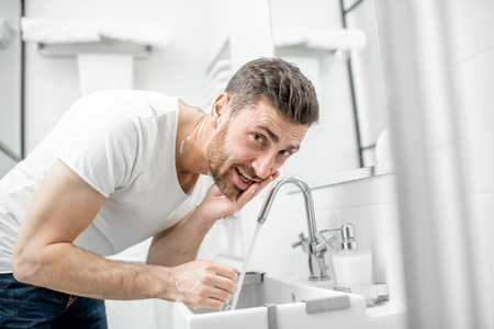Man washing his face with fresh water and foam in the sink at the white bathroom