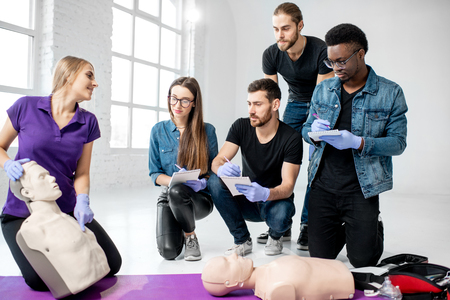 Group of young people learning to make artificial breathing with medical dummies during the first aid training in the white room Archivio Fotografico - 113402569