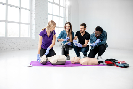 Group of young people learning to make artificial breathing with medical dummies during the first aid training in the white room Archivio Fotografico - 113402587