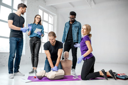Group of young people practising to make artificial breathing with instructor and medical dummies during the first aid training indoors