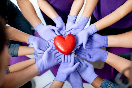 Group of people holding with hands in medical gloves red heart model. Close-up view. Healthy heart concept. Standard-Bild