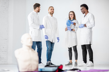 Group of young medics standing and talking together during the break of the first aid training with medical stuff and dummies on the floor