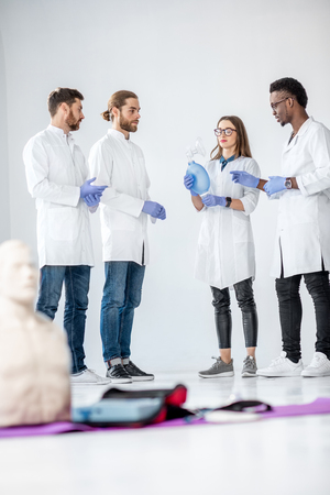 Group of young medics standing and talking together during the break of the first aid training with medical stuff and dummies on the floor Archivio Fotografico - 113403014
