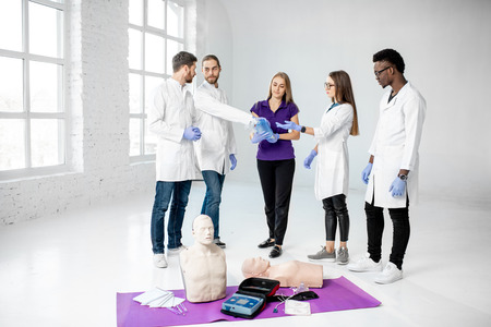 Group of young medics standing and talking together during the break of the first aid training with medical stuff and dummies on the floor Archivio Fotografico - 113403016