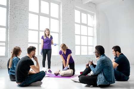Group of young people sitting in a circle during the first aid courses with two instructors training on medical dummies in the white spacious room Archivio Fotografico - 113403023