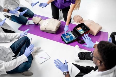 Instructor turning no the defibrillation and showing hands off during the first aid training with medics indoors, Close-up view with no face Stock Photo